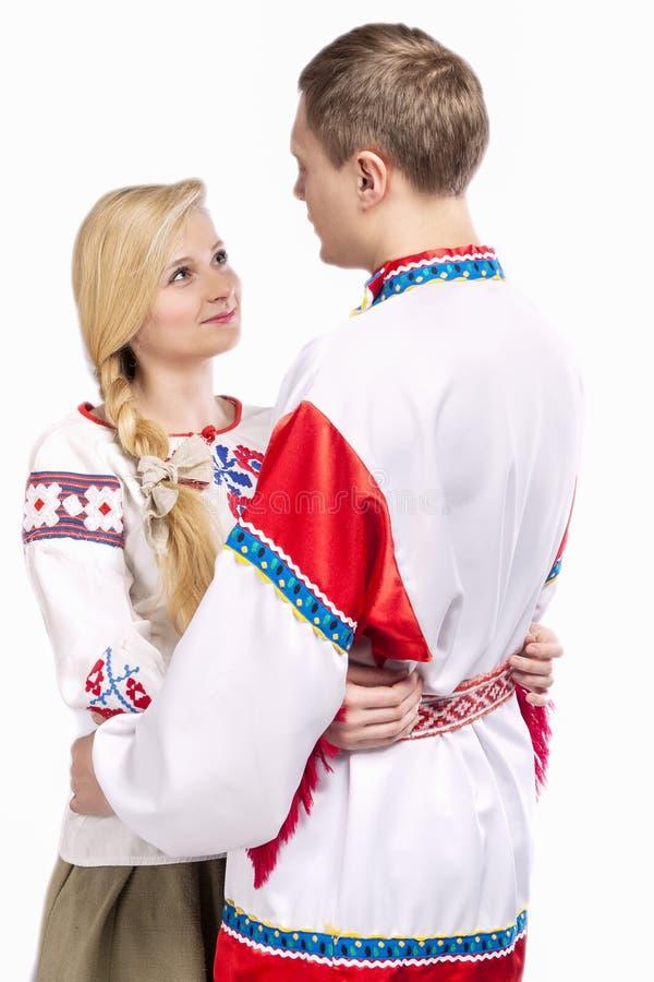 Портрет любить обнятых кавказских пар в национальных Belarussian и русских украшенных костюмах стоковые фотографии rf