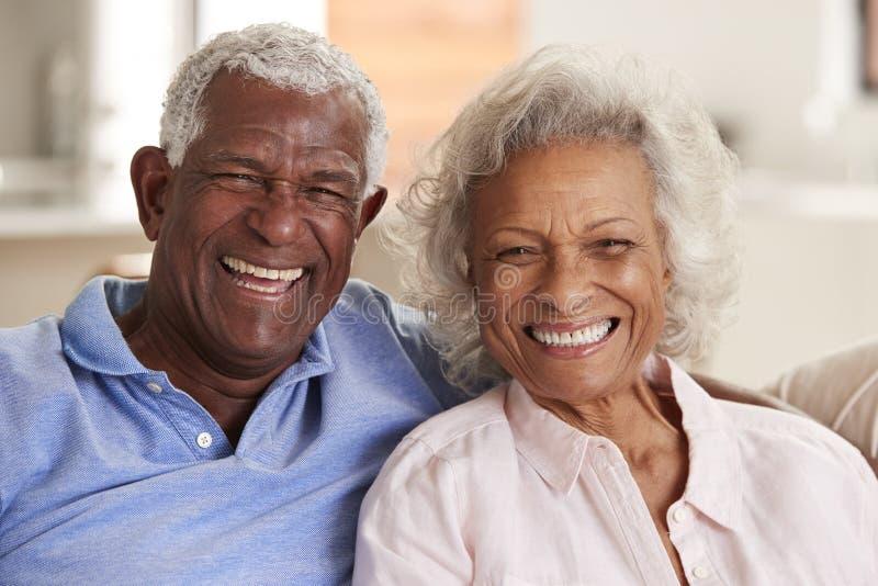 Портрет любить старших пар сидя на софе дома совместно стоковое фото rf