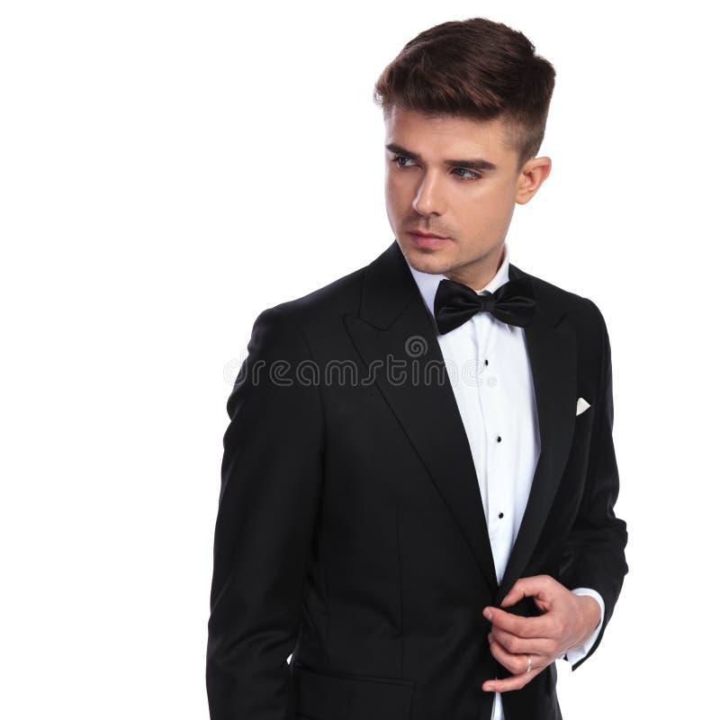 Портрет любопытного бизнесмена с bowtie unbuttoning его черный костюм стоковые фото