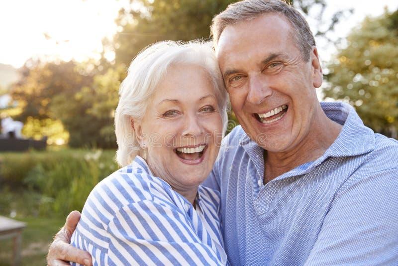 Портрет любящих старших пар обнимая Outdoors в парке лета против Flaring Солнца стоковые фото