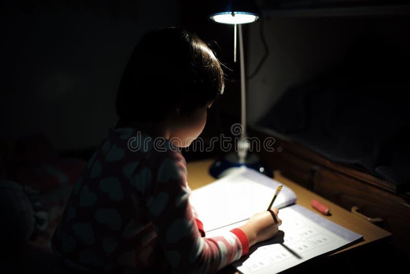 Портрет маленьких азиатских девушек делая ее домашнюю работу под ligh стоковое фото rf