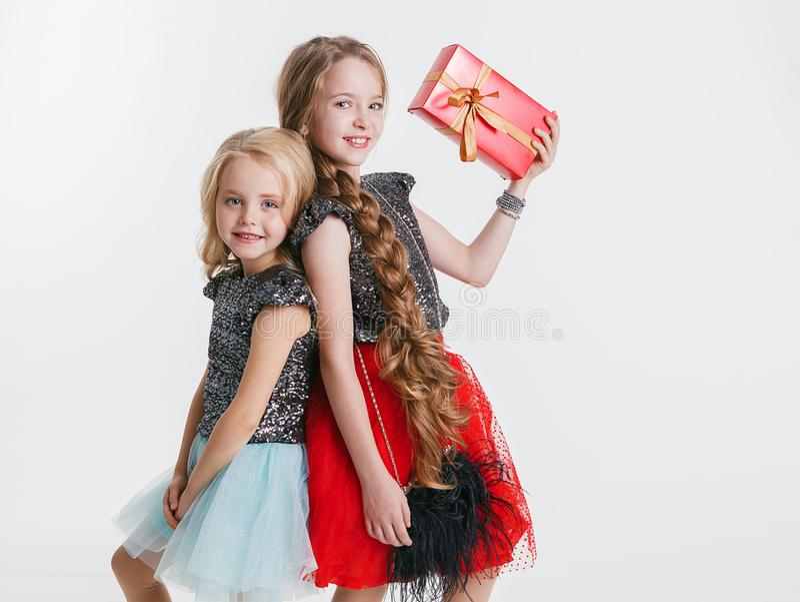 Портрет маленьких девочек при курчавый стиль причёсок стоя на партии праздника в платье с sequins, держа настоящий момент стоковые фото