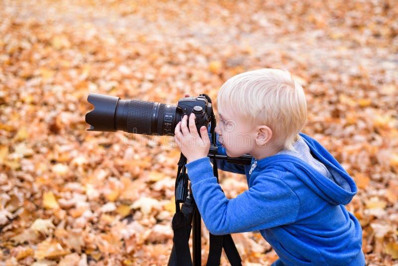 Портрет маленького блондинка с большой камерой DSLR на триподе. Фотосесс стоковое фото rf
