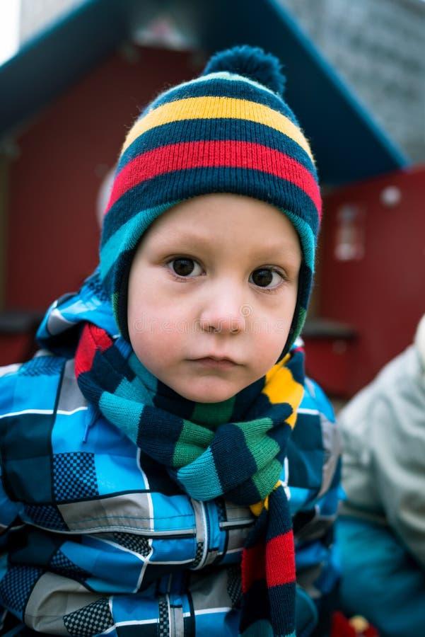 Портрет маленького унылого мальчика стоя на районе спортивной площадки стоковое фото rf