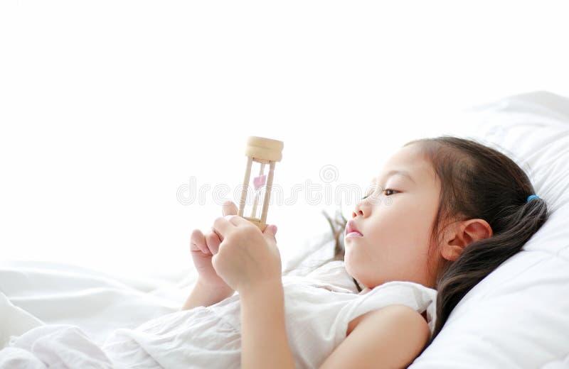 Портрет маленькой азиатской девушки смотря часы в руке лежа на кровати дома Времена ожидания с sandglass стоковая фотография