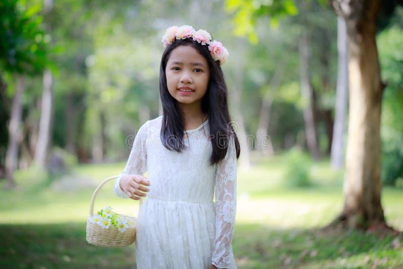 Портрет маленькой азиатской девушки усмехаясь в обрабатываемом лесе природы с мягким тоном стоковое изображение