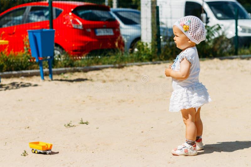 Портрет маленькой девочки в белом платье и белой шляпе с цветками на предпосылке автомобилей, на спортивной площадке, ребенок в стоковые фото