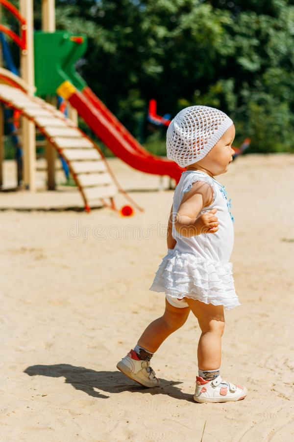 Портрет маленькой девочки в белом платье и белой шляпе с цветками на предпосылке, бежать вокруг места на спортивной площадке стоковое изображение rf