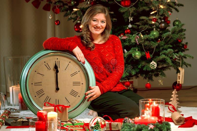 Портрет маленькой девочки в красном свитере с часами на предпосылке светов рождества стоковое изображение rf