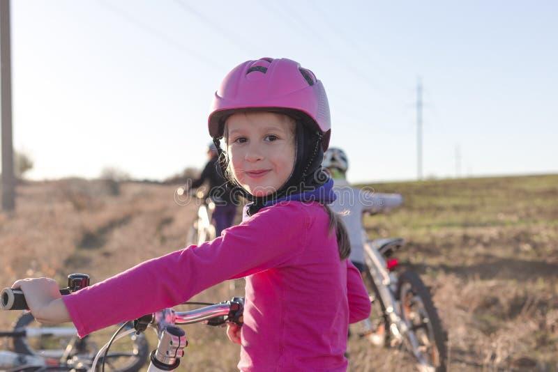 Портрет маленькой девочки в шлеме с велосипедом стоковые изображения