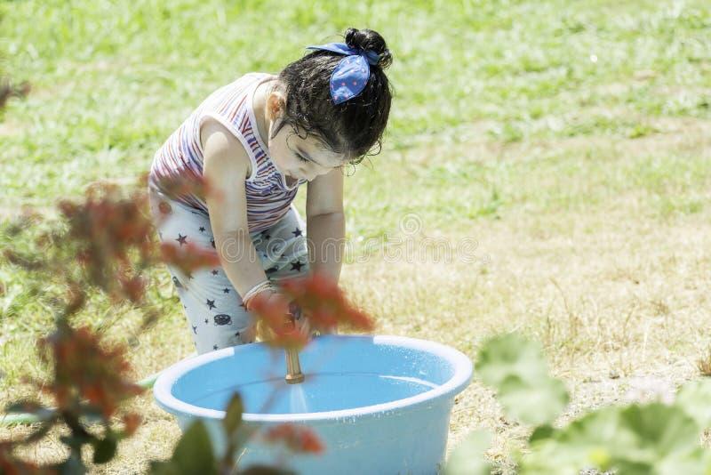 Портрет маленькой девочки играя со шлангом и голубым пластиковым ушатом стоковая фотография