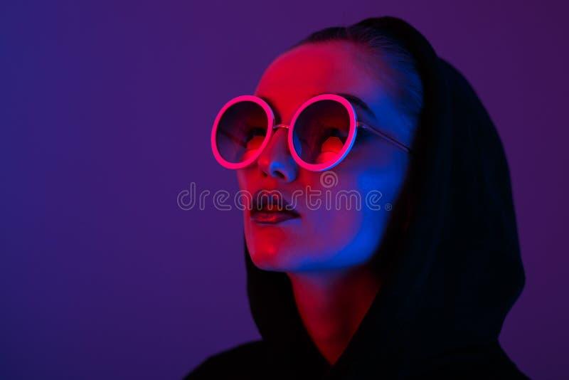 Портрет маленькой девочки моды в черном свитере с клобуком и круглыми солнечными очками в красном и голубом неоновом свете в стоковые фото
