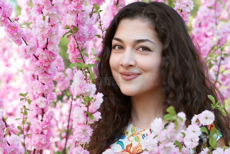 Портрет маленькой девочки на пинке цветет предпосылка, поднимающее вверх стороны близкое стоковые фото