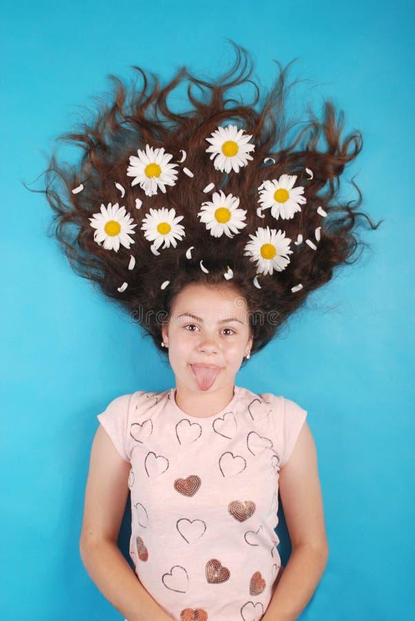 Портрет маленькой девочки с маргаритками в их волосах лежа на поле стоковое изображение rf