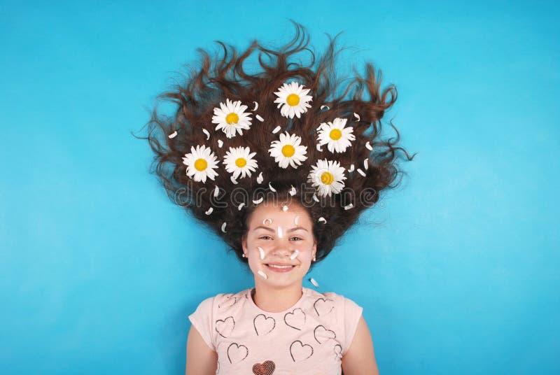 Портрет маленькой девочки с маргаритками в их волосах лежа на поле стоковые фотографии rf
