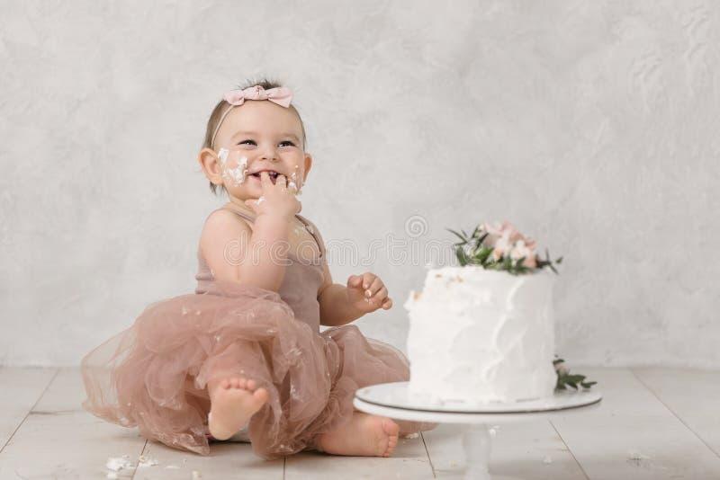 Портрет маленькой жизнерадостной девушки дня рождения с первым тортом Еда первого торта Торт огромного успеха стоковое изображение