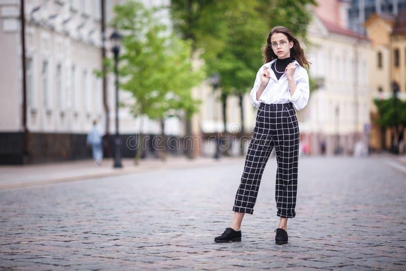 Портрет маленькой красивой стильной девушки ребенк с солнечными очками и короткими брюками шотландки в улице города городской стоковая фотография rf
