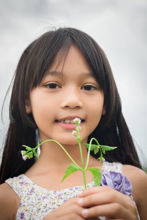 Портрет маленькой милой азиатской девушки держа цветок среди фиолетового взгляда на камере, свободы поля цветка стоковое фото