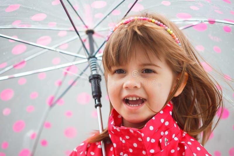 Портрет маленькой милой девушки в красном пальто дождя под зонтиком стоковые изображения