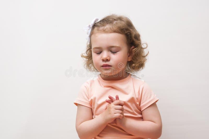 Портрет маленькой милой девушки которая молит или мечтает стоковые изображения rf