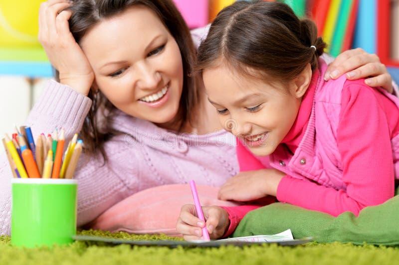Портрет маленькой милой девушки с чертежом матери стоковое изображение