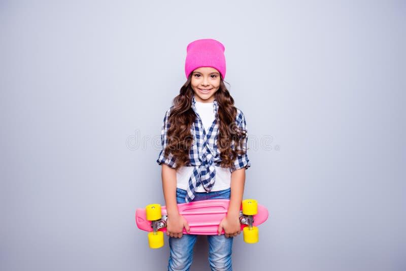 Портрет маленькой милой усмехаясь девушки с розовым скейтбордом в pi стоковые фото