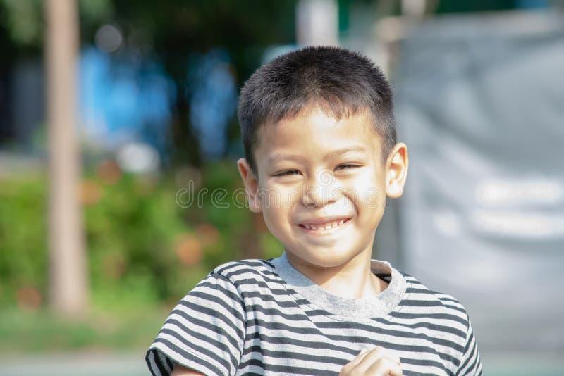 Портрет мальчика Азии, смеясь и усмехаясь счастливо в парке стоковая фотография