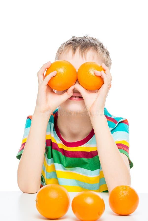 портрет мальчика который играет с апельсинами, съемка в студии на белом стоковое фото