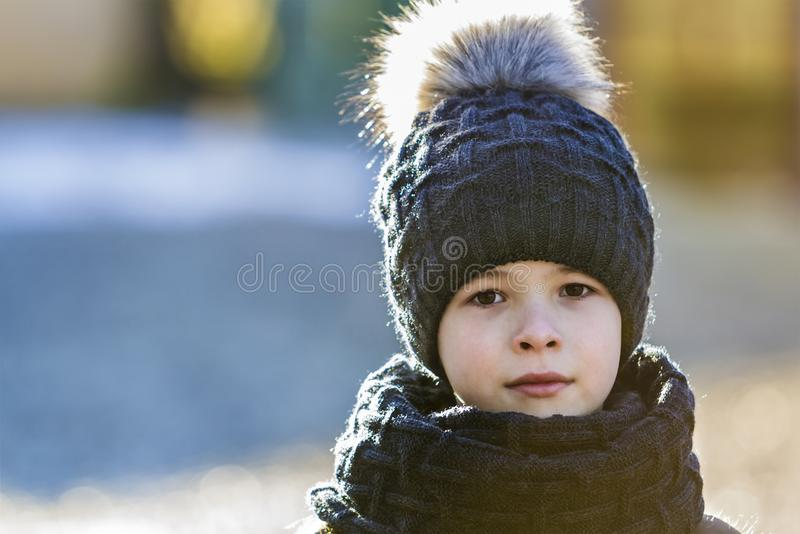 Портрет мальчика ребенка в шляпе и шарфе outdoors в солнечной зиме стоковое фото rf