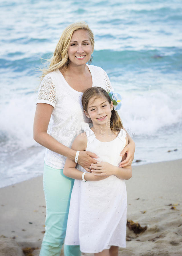 Портрет матери и дочери на пляже стоковое изображение