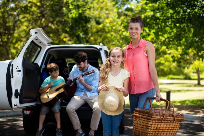 Портрет матери и дочери стоя с корзиной пикника пока отец и сын играя гитару в b стоковая фотография rf