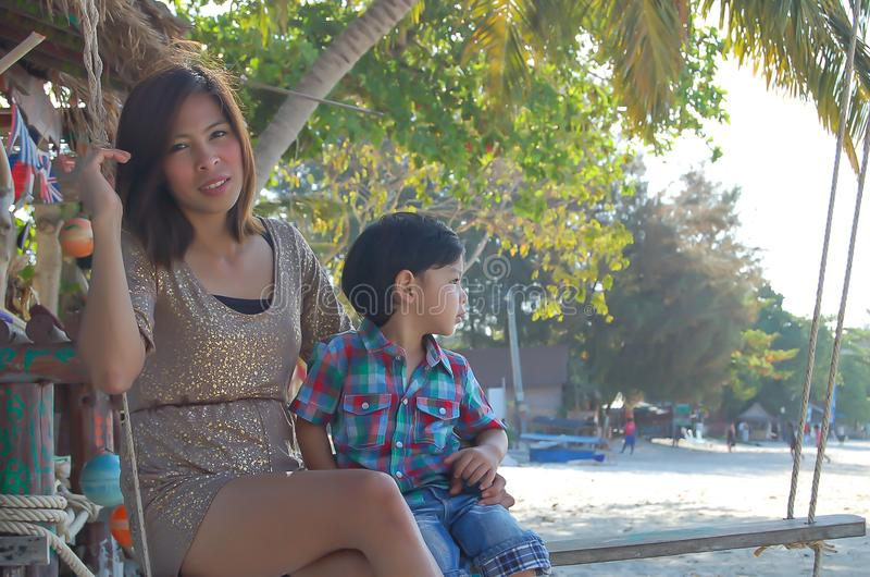 Портрет матери и сына играя стул качания в море стоковые изображения