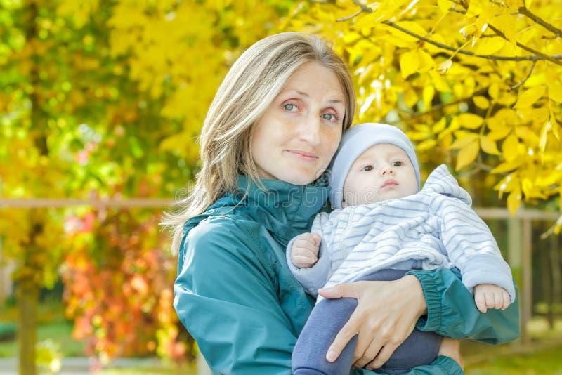 Портрет матери осени внешний счастливый держа ее младенца на желтом shrubbery осени выходит предпосылка стоковое изображение