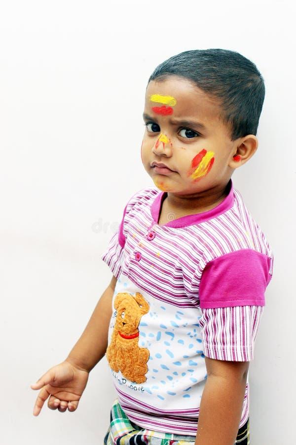 Портрет маленького ребенка на фестивале Holi изолированного на белой предпосылке стоковое фото