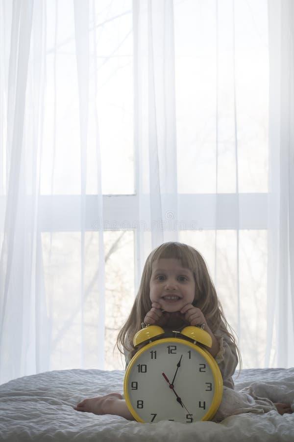 Портрет маленькой девочки на огромном будильнике перед окном над белизной стоковое фото rf