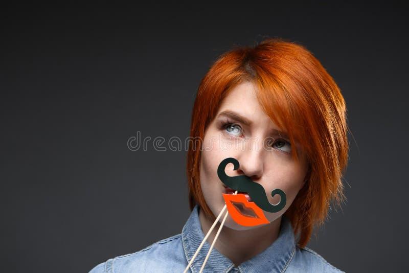 Портрет маленькой девочки нося поддельные усик и губы над серым цветом стоковое изображение