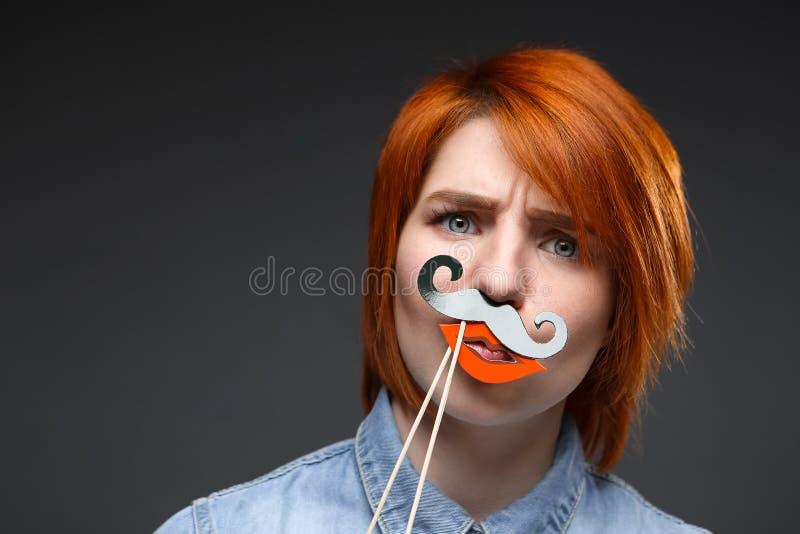 Портрет маленькой девочки нося поддельные усик и губы над серым цветом стоковая фотография