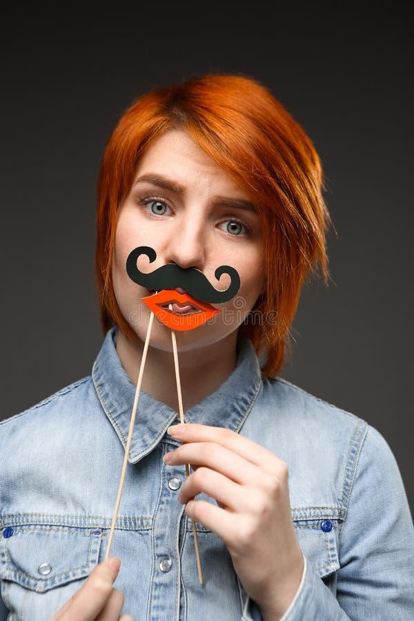 Портрет маленькой девочки нося поддельные усик и губы над серым цветом стоковые фотографии rf