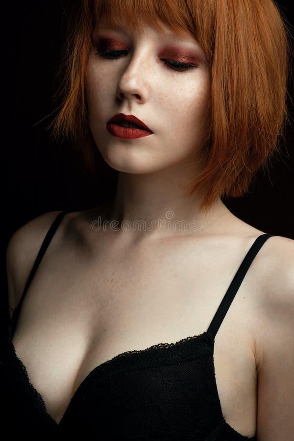 Портрет маленькой девочки с красными волосами и веснушками с красными губами и закрытыми глазами при темный состав смотря камеру стоковые фотографии rf