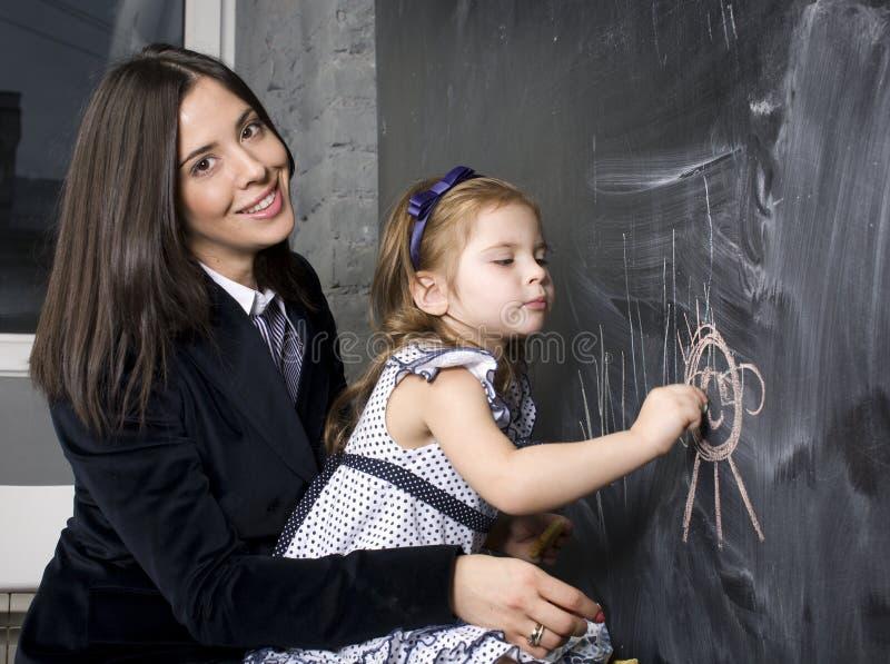 Портрет маленькой девочки с матерью на классн классном, делая уроки стоковая фотография rf