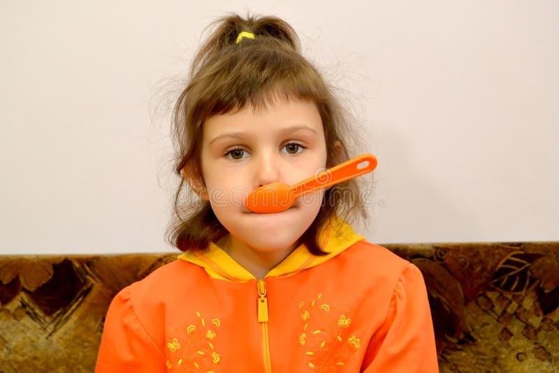 Портрет маленькой девочки с пластичной ложкой в рте стоковое фото