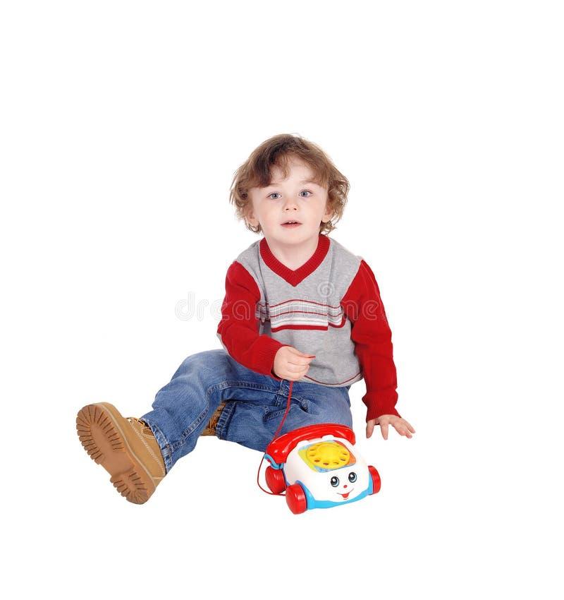 Портрет мальчика с его телефоном игрушки стоковое фото