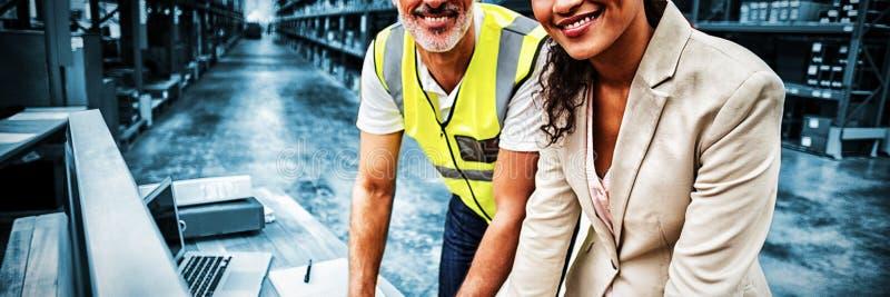 Портрет менеджера и работника склада работая совместно стоковая фотография