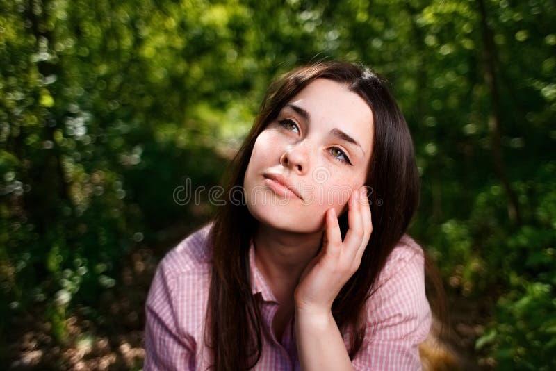 Портрет мечтательной молодой женщины с рукой над стороной стоковое изображение