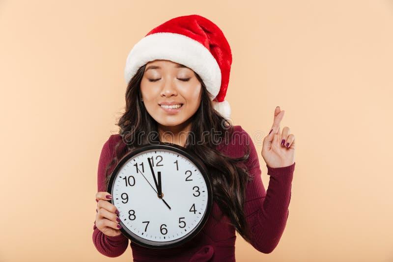 Портрет мечтая девушки в шляпе Санта Клауса красной держа часы s стоковая фотография