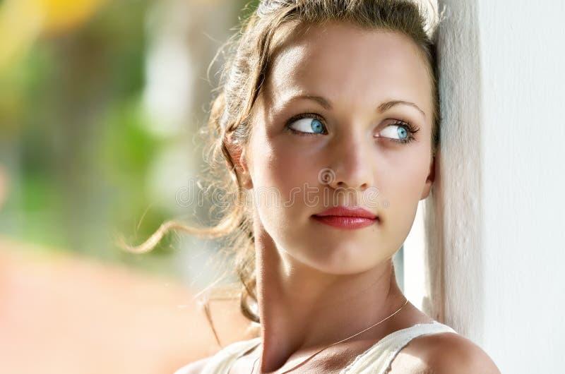 Портрет мечтая девушки с голубыми глазами стоковая фотография