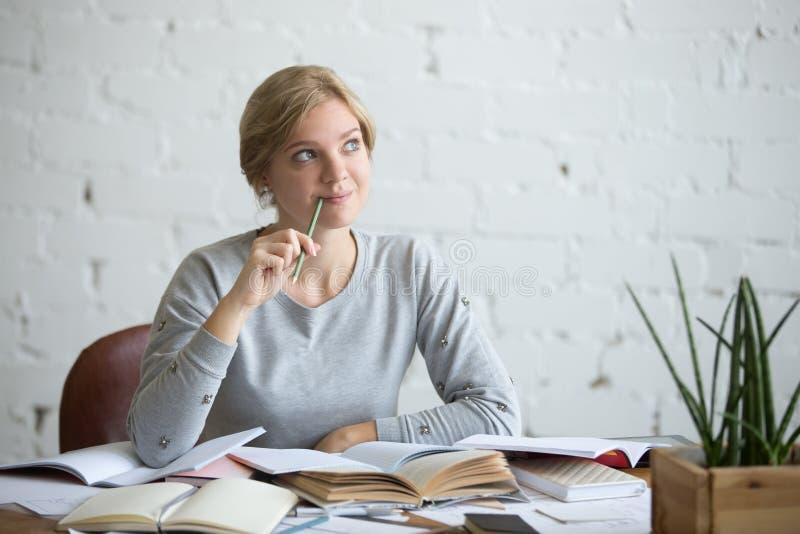 Портрет мечтая женщины студента на столе стоковая фотография