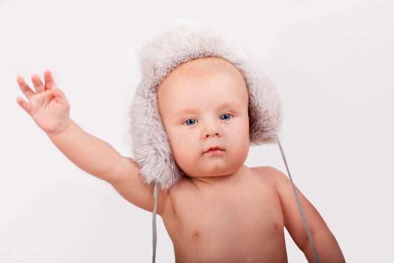 Портрет милого кавказского младенца 9 месяцев годовалых при голубые глазы нося меховую шляпу на светлом удерживании предпосылки стоковое фото rf