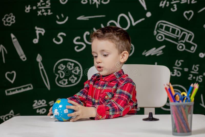 Портрет милого маленького мальчика, держащего в руках маленький глобус на заднем плане Готово к школе Вернуться в школу стоковые фото
