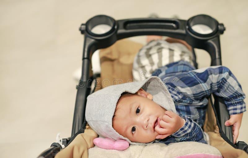 Портрет милого маленького ребенка с клобуком на голове лежа на прогулочной коляске со смотреть камеру стоковое изображение